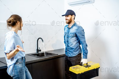Handy man with woman on the kitchen