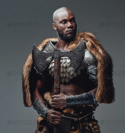 Bearded black skinned barbarian with fur and shaved head holding an axe