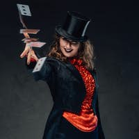 Smiling tricky woman with top hat throws cards in dark background