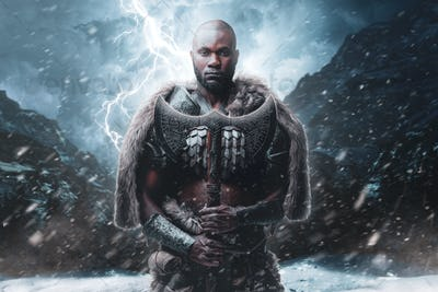 Proud viking with black skin holding his axe in stormy mountains