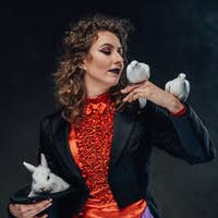 Caucasian woman with charming rabbit and doves in dark background