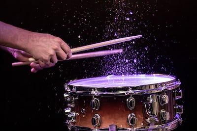 Drum sticks hitting snare drum with splashing water on black background under studio lighting.