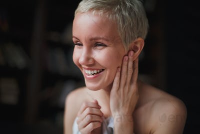 Laughing beautiful young woman with blond short hair sitting on bed on white linen