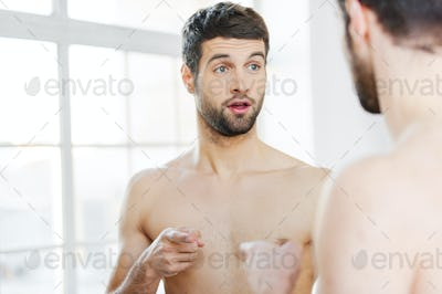 Who am I? Frustrated young shirtless man pointing himself while standing against a mirror