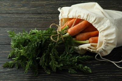 Bag with fresh carrot on wooden background
