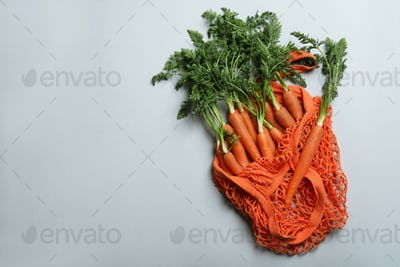 String bag with carrot on light gray background