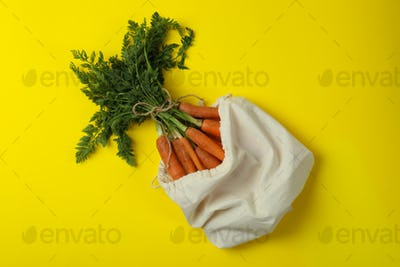Bag with fresh carrot on yellow background