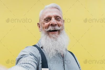 Happy hipster senior man taking a selfie outdoors in the city - Focus on face