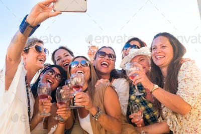 Beautiful group of women toasting on the terrace celebrating a birthday and taking a selfie