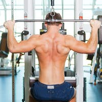 Training his body to perfection. Rear view of young muscular man working out on bench press