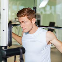 Strong and motivated. Handsome young muscular man working out on bench press