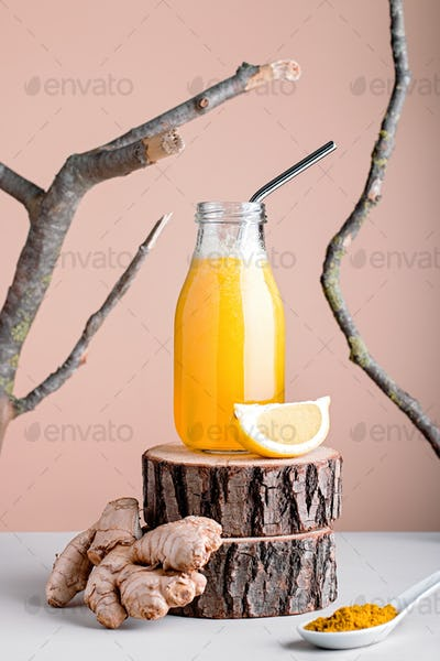 Ginger smoothie with turmeric and lemon on wooden riser