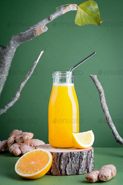 Immune boosting ginger and turmeric smoothie on green background