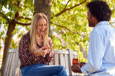 Mature Man Kneeling And Proposing To Surprised Woman Sitting In Park With Engagement Ring In Box