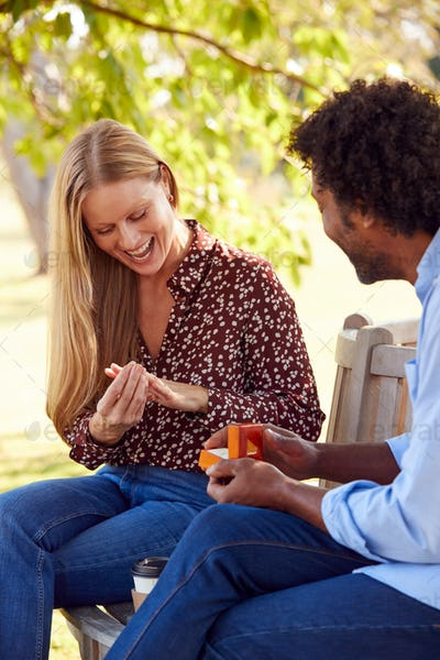Romantic Mature Man Proposing To Surprised Woman Sitting On Park Bench With Engagement Ring In Box