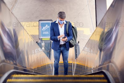 Businessman On Escalator At Railway Station With Mobile Phone Wearing PPE Face Mask During Pandemic