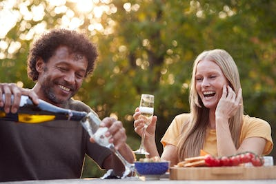 Mature Man Pouring Champagne As Couple Celebrate Sitting At Table In Garden With Snacks