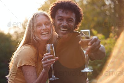 Portrait Of Mature Couple Celebrating Outdoors With Champagne Against Flaring Evening Sun