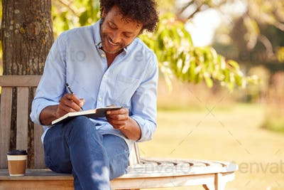 Mature Man With Takeaway Coffee Sitting On Park Bench Under Tree Writing In Notebook
