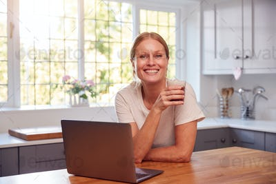 Portrait Of Mature Woman Wearing Fitness Clothing At Home In Kitchen Logging Activity On Laptop