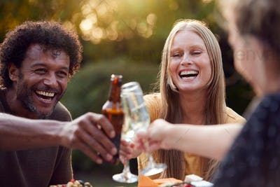 Group Of Friends Celebrating With Beer And Champagne As They Sit At Table In Garden With Snacks