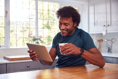 Mature Man Wearing Fitness Clothing At Home Logging Activity From Smart Watch Onto Laptop