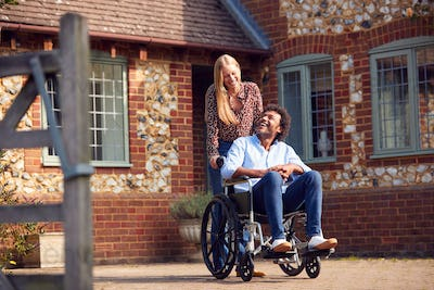 Mature Couple With Man Sitting In Wheelchair Being Pushed By Woman Outside Home