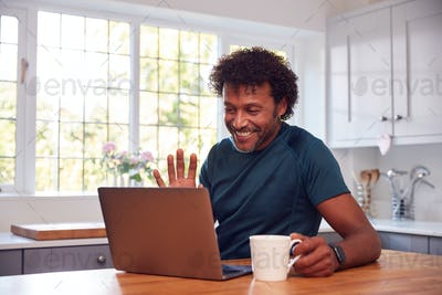 Mature Man At Home In Kitchen Waving As He Makes Video Call On Laptop Computer