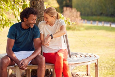 Couple Wearing Fitness Clothing Sitting On Seat Under Tree Checking Activity Monitor On Smartwatch