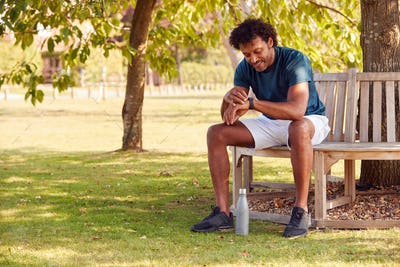 Man Wearing Fitness Clothing Sitting On Seat Under Tree Checking Activity Monitor On Smartwatch