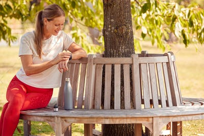 Woman Wearing Fitness Clothing Sitting On Seat Under Tree Checking Activity Monitor On Smartwatch