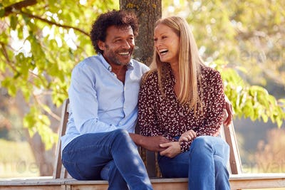 Loving Mature Couple Relaxing Sitting Together On Bench Under Tree In Summer Park Or Garden