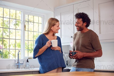 Couple With Pregnant Wife In Kitchen Talking And Drinking Coffee Together