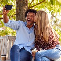 Kissing Mature Couple Posing For Selfie On Mobile Phone Sitting On Seat In Park