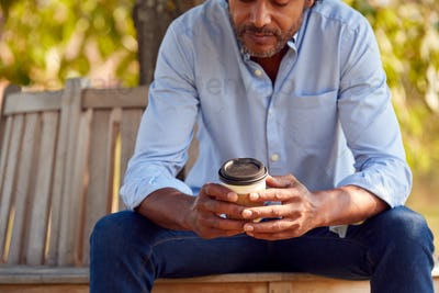 Close Up Of Mature Man Sitting On Park Bench Under Tree Holding Takeaway Coffee Cup