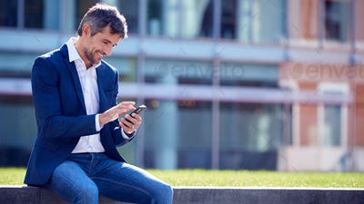 Businessman On A Break Sitting Outside Office Using Mobile Phone