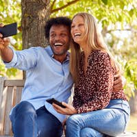 Loving Mature Couple Posing For Selfie On Mobile Phone Sitting On Seat In Park