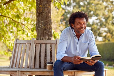 Mature Man Relaxing Sitting On Park Bench Under Tree Reading Book With Takeaway Coffee