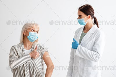 Doctor And Vaccinated Senior Female Gesturing Thumbs-Up After Vaccination