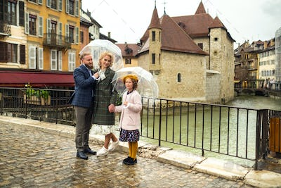 Beautiful family with umbrellas in rainy weather in Annecy. France.Family walk in the rain