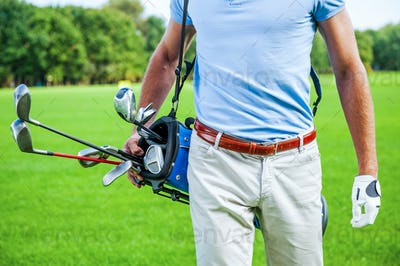 Ready to play. Close-up of male golfer carrying golf bag with drivers while walking by green grass