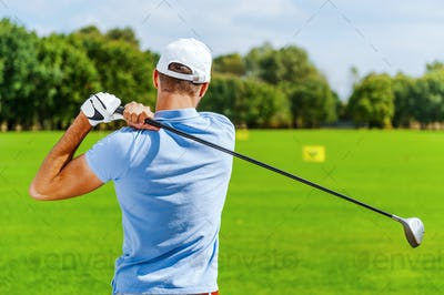 Good strike. Rear view of male golfer playing golf while standing on green