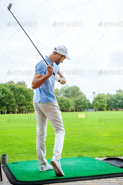 Teeing off. Full length rear view of young male golfer playing golf