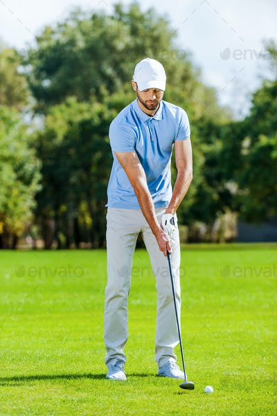 Preparing for shot. Full length of young man in sports clothing playing golf while standing on green