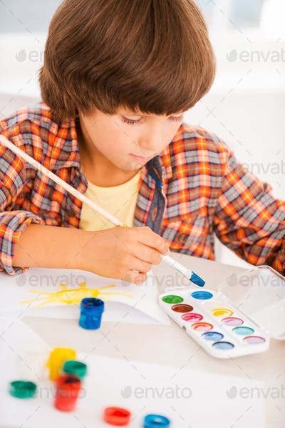 Boy painting. Little boy relaxing while painting with watercolors sitting at the table