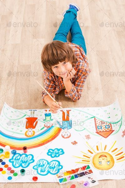 Boy painting. Young boy relaxing while painting with watercolors lying on the floor