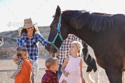 Happy family enjoy day outdoor at ranch with horses - Parents, children and animal love