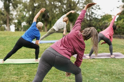 Multiracial people doing yoga at park with social distance for coronavirus outbreak