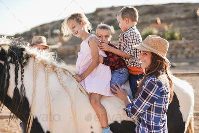Children of horseback riding - Family enjoy day at ranch outdoor - Human and animal love
