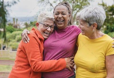Happy multiracial senior women having fun together at park